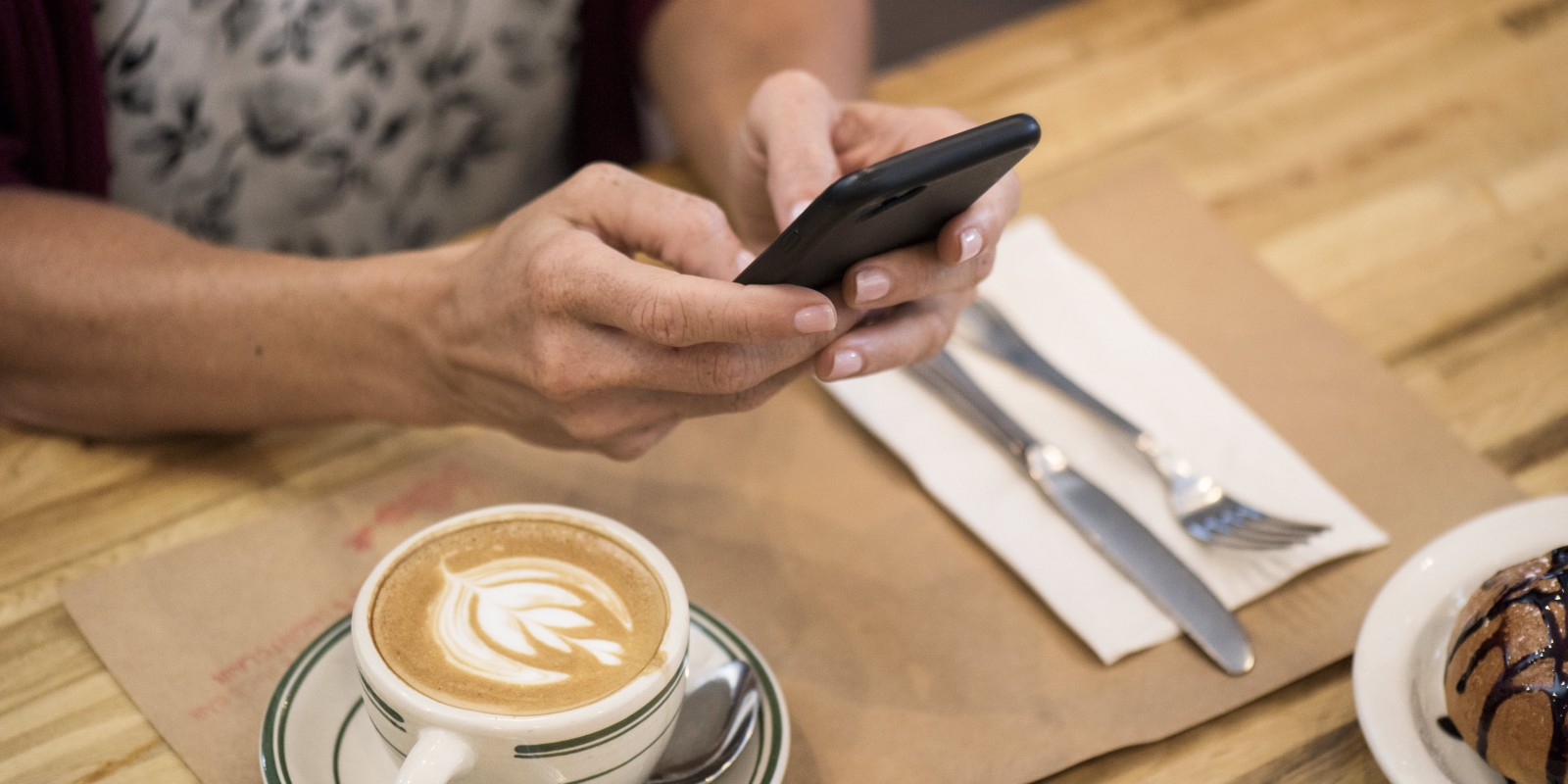 Woman with coffee holding phone